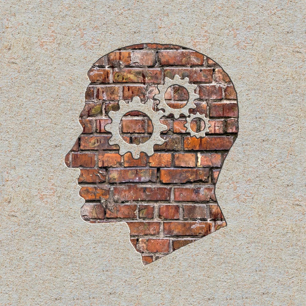 Psychological Concept - Profile of Head with Cogwheel Gear Mechanism on the Brick and Plastered Wall.
